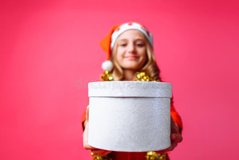 Um adolescente no chapéu e no ouropel do Natal do ` s de Santa em torno de seu ne foto de stock royalty free