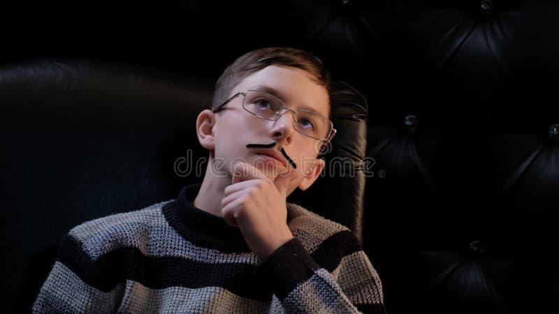 Um adolescente nos vidros com o a colar-no bigode, vestindo uma camiseta, senta-se em uma cadeira e olha-se acima pensativamente  imagens de stock royalty free