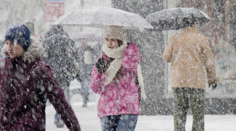 Um adolescente que anda sob o guarda-chuva na queda de neve pesada imagem de stock