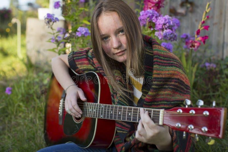 Um adolescente que joga a guitarra acústica imagem de stock royalty free