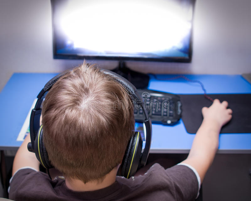 Um adolescente que joga um jogo de computador em casa fotografia de stock royalty free