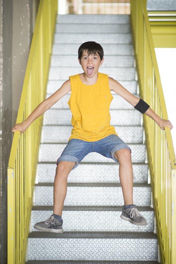Um adolescente que salta nas escadas e no sorriso fotografia de stock