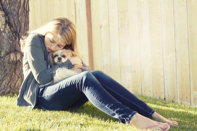 Um adolescente triste ou deprimido que abraça um cão pequeno fotografia de stock royalty free