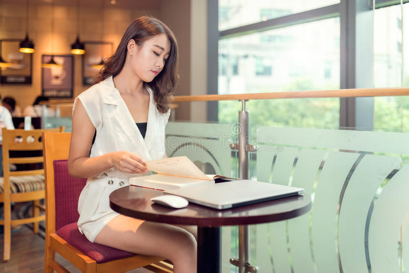 Um adulto novo asiático bonito está lendo um livro fotografia de stock