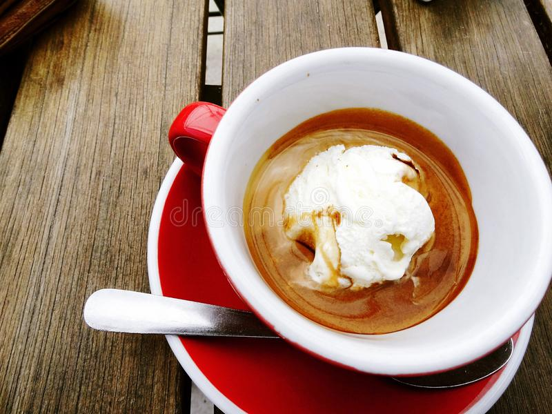 Um affogato (café quente do café derramado sobre o gelado), servido no copo e em uns pires vermelhos fotografia de stock royalty free