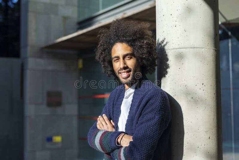 Um afro-americano elegante bonito novo est? perto de uma coluna Um estudante nas cal?as de brim e em um casaco azul com um pentea imagem de stock