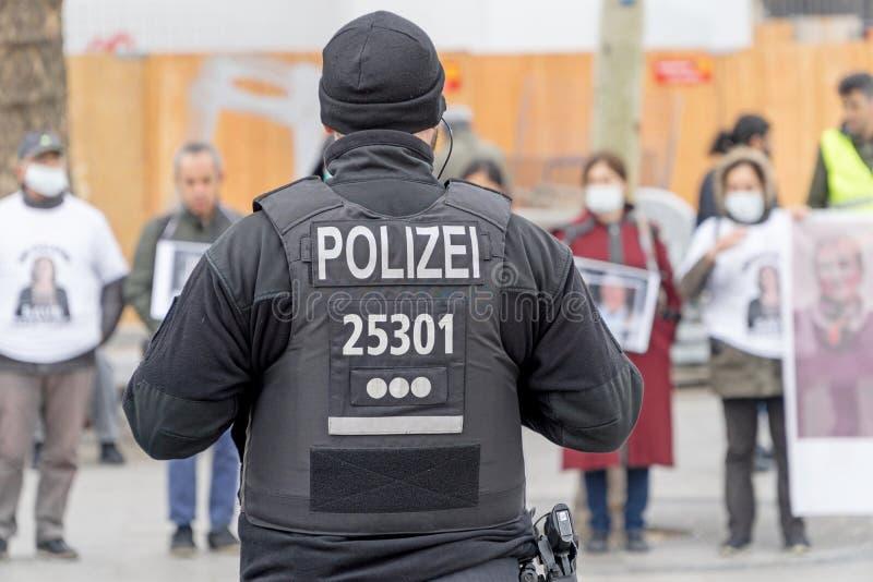 Um agente da polícia alemão que está na frente de um grupo de protestors imagem de stock royalty free
