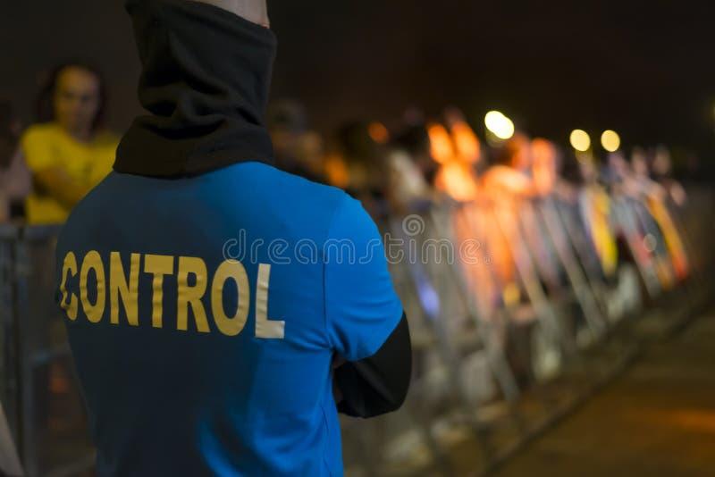 Um agente da segurança na cerca dos fãs imagem de stock royalty free