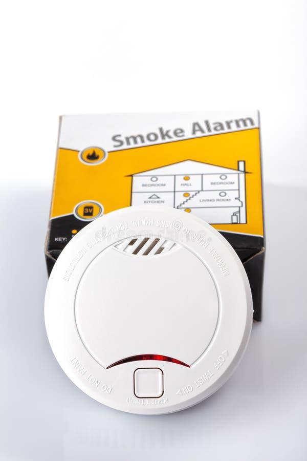 Um alarme de fumo com sua caixa isolada no branco fotos de stock royalty free