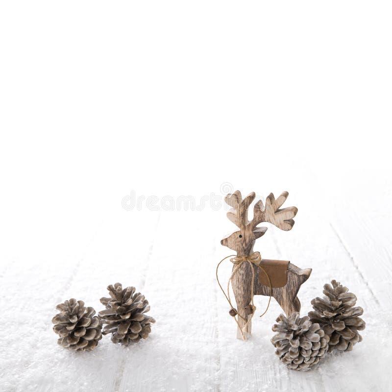 Um alce cinzelado de madeira isolado no fundo nevado branco para o chr imagem de stock