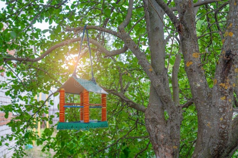 Um alimentador para os p?ssaros feitos numa forma de uma casa em um jardim fotos de stock