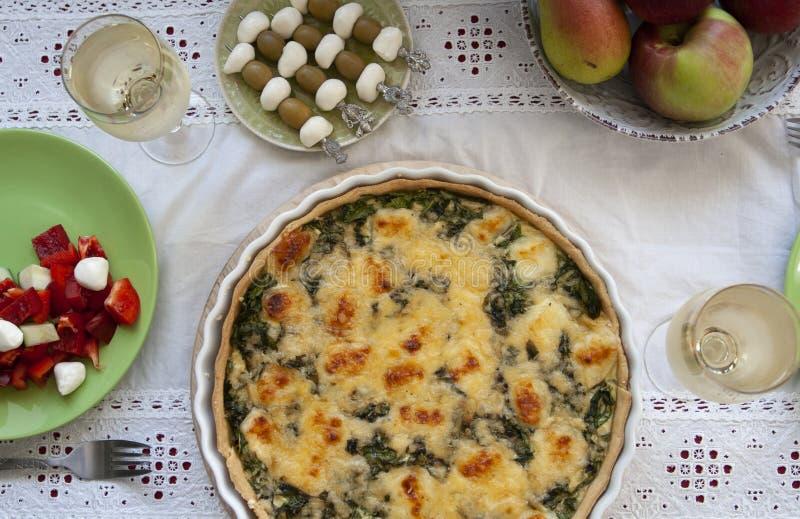 Um almo?o gourmet: torta dos espinafres com queijo, uma bacia de frutos, uma salada e vinho foto de stock royalty free