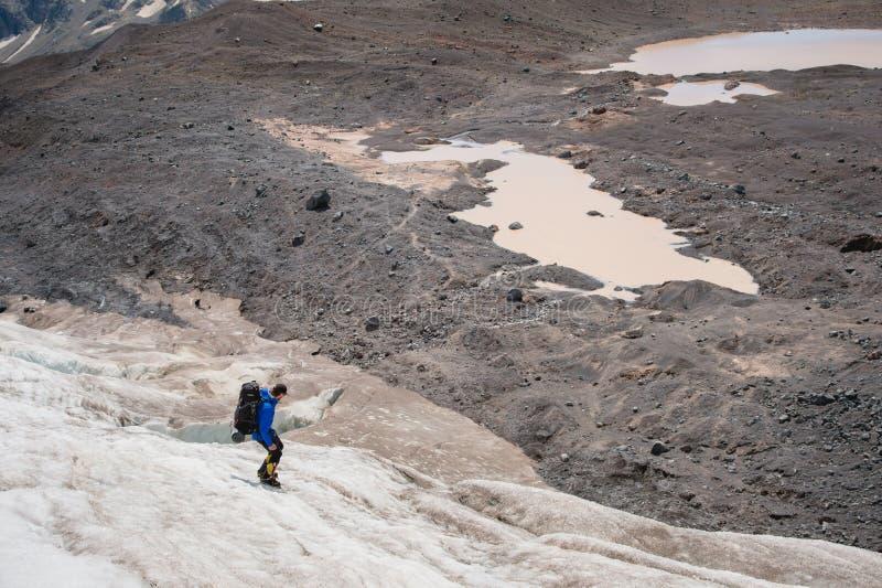 Um alpinista com uma trouxa anda nos ganchos de ferro que anda ao longo de uma geleira empoeirada com os passeios nas mãos entre  fotos de stock
