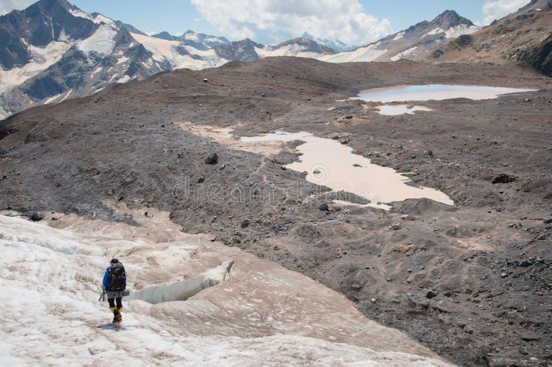 Um alpinista com uma trouxa anda nos ganchos de ferro que anda ao longo de uma geleira empoeirada com os passeios nas mãos entre  fotografia de stock