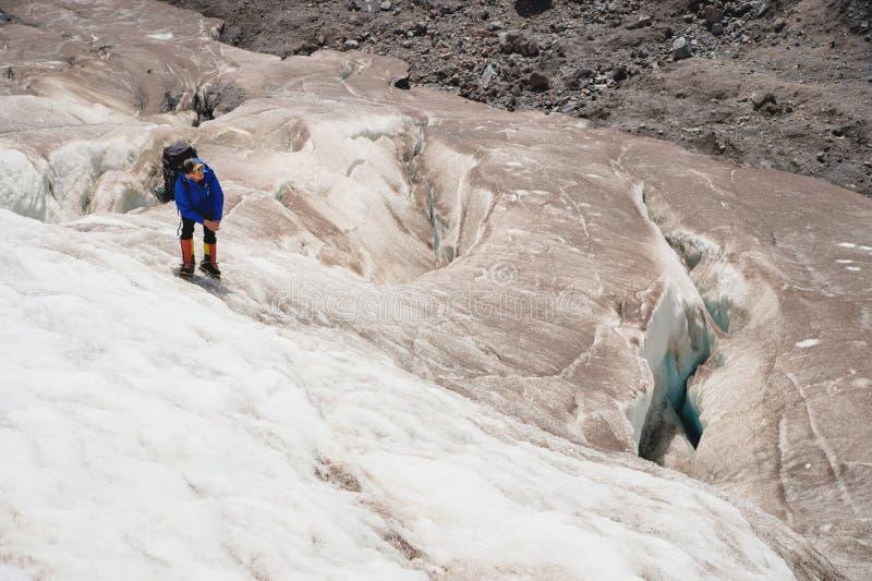 Um alpinista com uma trouxa anda nos ganchos de ferro que anda ao longo de uma geleira empoeirada com os passeios nas mãos entre  foto de stock