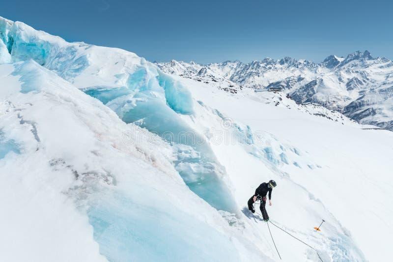 Um alpinista profissional em uma máscara do capacete e de esqui no seguro faz um entalhe-furo na geleira contra o contexto foto de stock