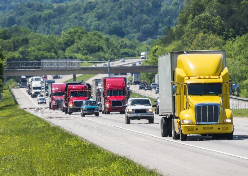 Um amarelo conduz semi uma linha embalada de tráfego abaixo de um de um estado a outro em Tennessee fotos de stock