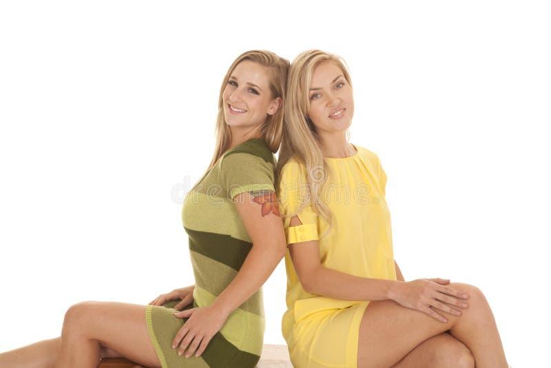 Um amarelo verde de duas mulheres senta o sorriso imagens de stock royalty free