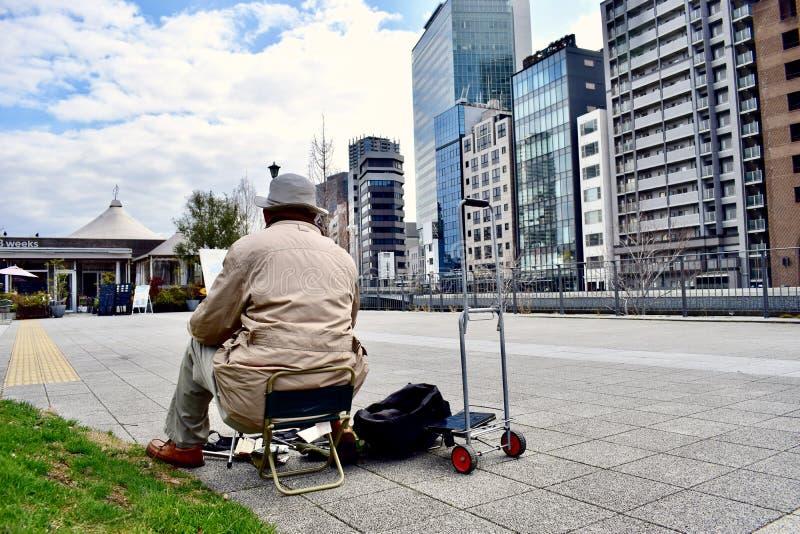 Um ancião está tirando uma imagem de prédios de escritórios do distrito financeiro de Japão Osaka imagem de stock