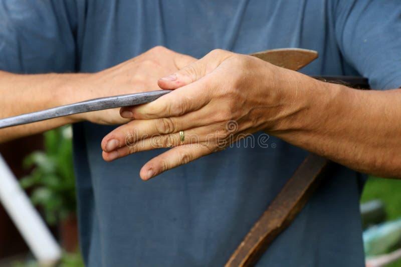 Um ancião que aponta a borda de aço da foice com mó molhada fotos de stock royalty free
