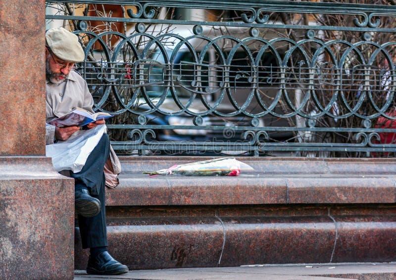Um ancião que lê o papel da notícia pelo monumento a Peter Tchaikovsky Turistas que andam em torno de Moscou imagem de stock