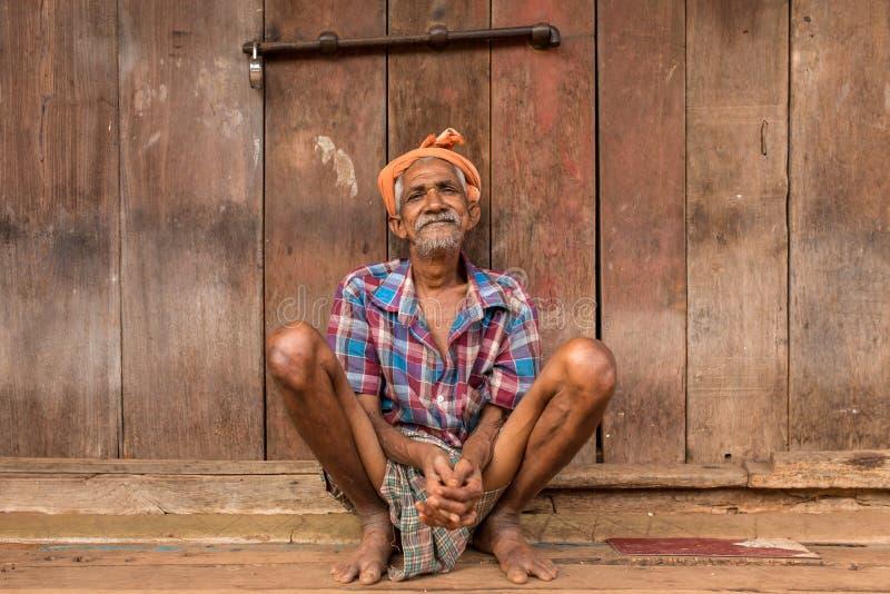 Um ancião que senta-se perto da parede de madeira em Gokarna, Índia fotografia de stock royalty free