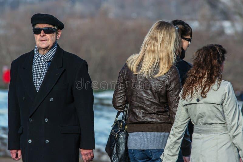Um ancião que veste o revestimento preto e os óculos de sol que andam no parque imagem de stock royalty free
