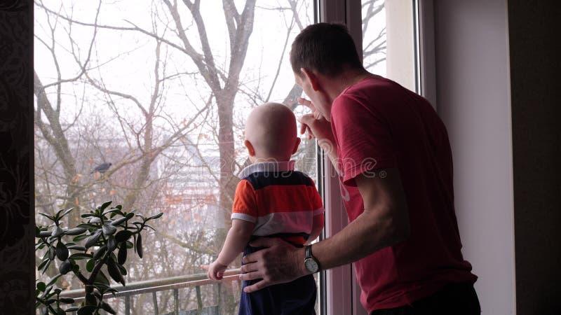 Um anci?o e seu neto pequeno ador?vel est?o jogando pela janela e pela mostra de primeira gera??o ao beb? um p?ssaro no fotografia de stock