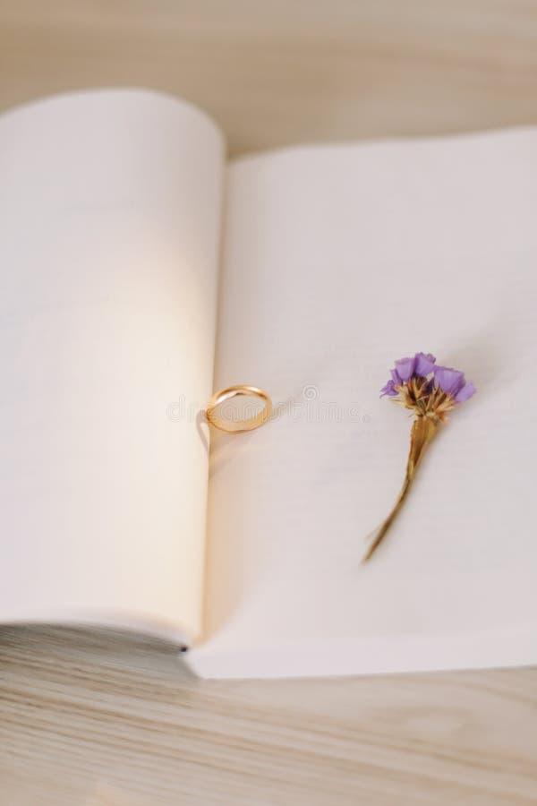 Um anel de noivado no fundo de um livro e de uma flor Proposta de uni?o Detalhes do casamento imagens de stock