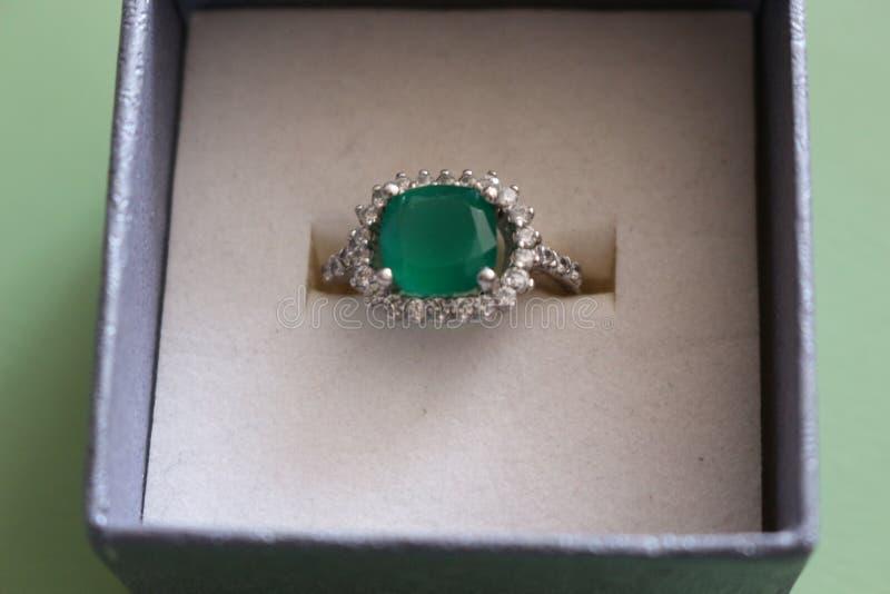 Um anel de prata com uma grande pedra verde e Fionites pequeno em torno dele imagem de stock royalty free