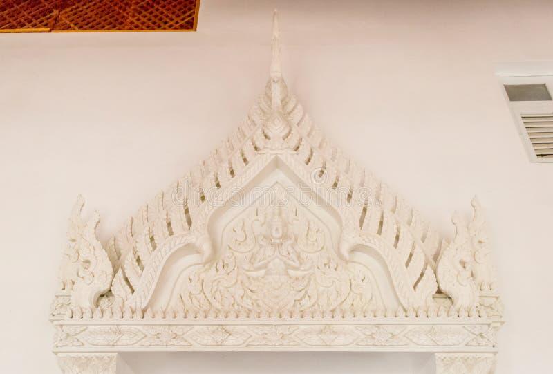 Um anjo branco scultured na parede branca na proibição tailandesa do templo fotografia de stock