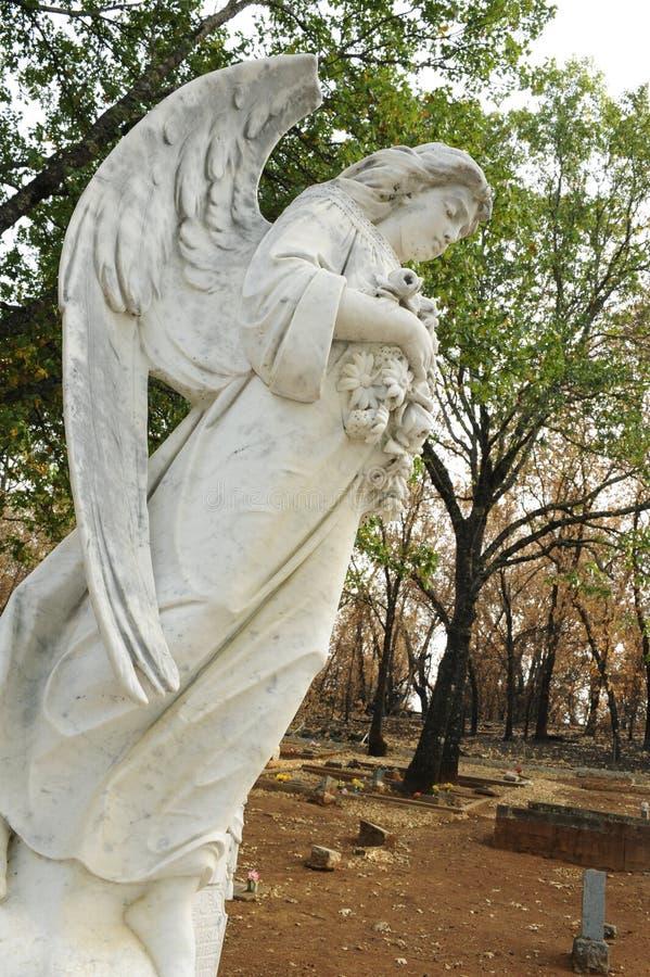 Um anjo está entre um cemitério queimado no rescaldo de um fogo fotografia de stock royalty free