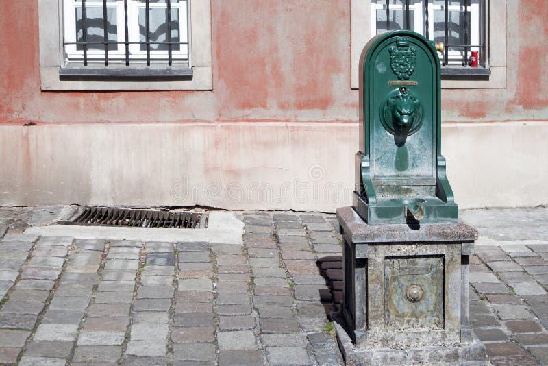 Um antigo antigo público bem, fonte bebendo Coluna com água potável ao longo da rua da cidade, cidade velha foto de stock royalty free