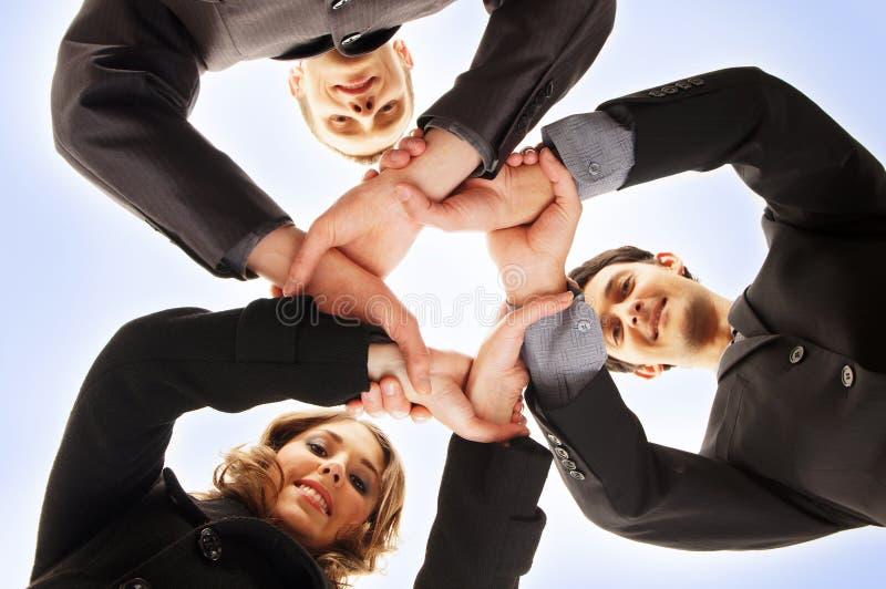 Um aperto de mão do grupo entre três pessoas do negócio imagem de stock