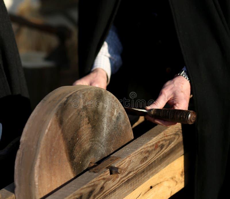 Um apontador de faca mais velho aponta sua faca fotografia de stock royalty free