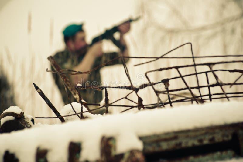 Um arame farpado e um soldado no uniforme com uma arma visam o tiro Figura borrada no fundo Boina azul fotografia de stock