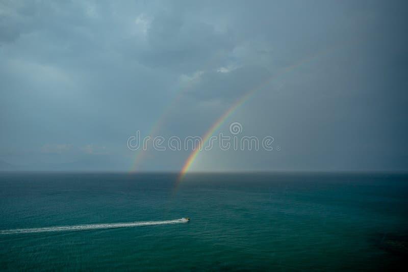Um arco-íris dobro acima da superfície de um mar tormentoso com um cavaleiro em um 'trotinette' da água fotografia de stock royalty free
