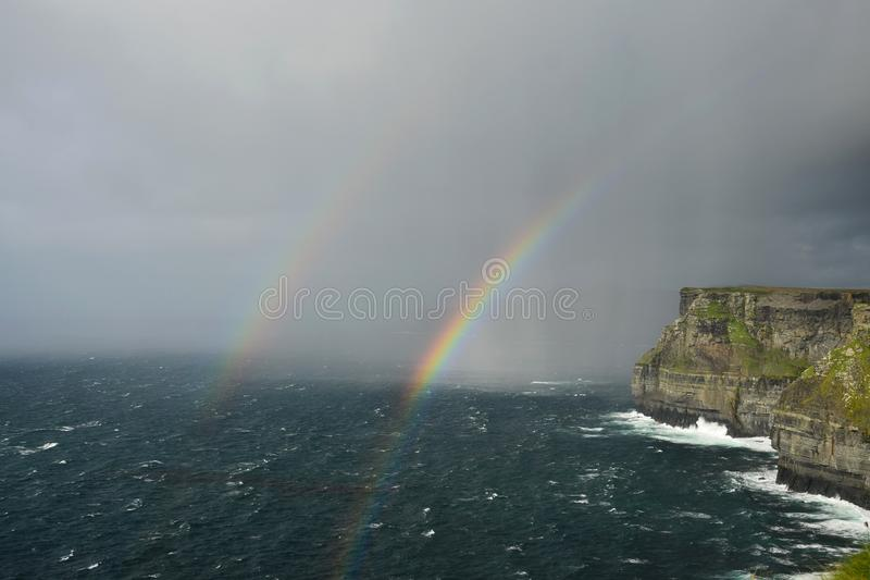 Um arco-íris dobro sobre os penhascos de Moher na Irlanda foto de stock