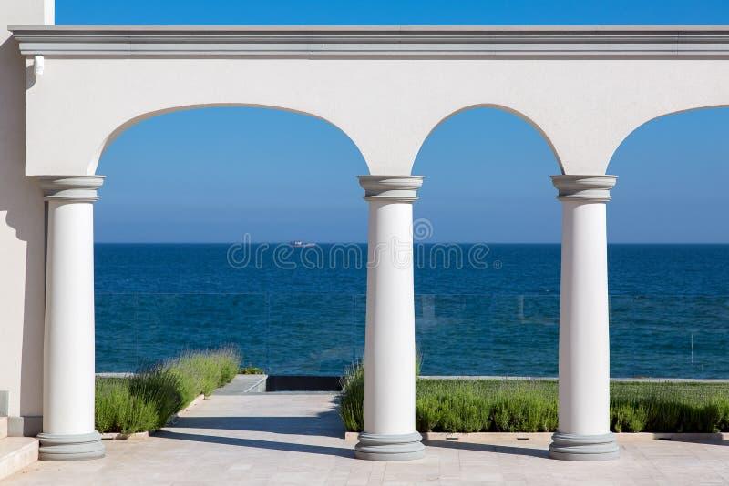 Um arco com colunas da pedra branca e de um assoalho de mármore imagem de stock