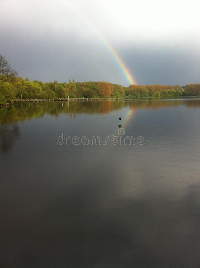 Um arco-?ris com reflex?o sobre o lago Umminger, Alemanha imagem de stock royalty free