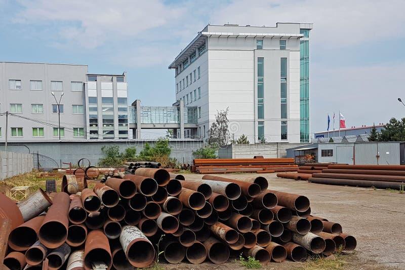 Um armazém das tubulações do metal de vários tamanhos sob o céu aberto Tecnologias da indústria da construção civil Transporte do fotografia de stock