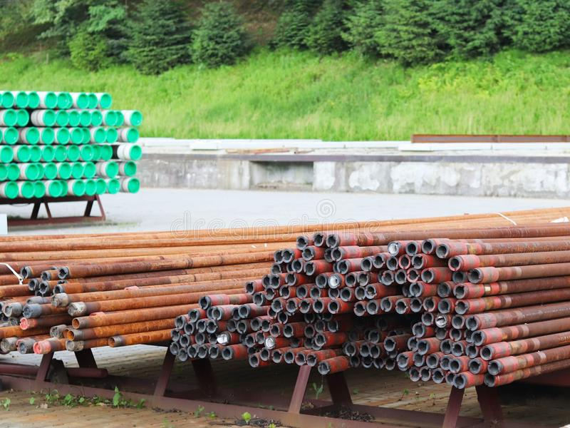 Um armazém das tubulações do metal de vários tamanhos sob o céu aberto Tecnologias da indústria da construção civil Transporte do imagens de stock