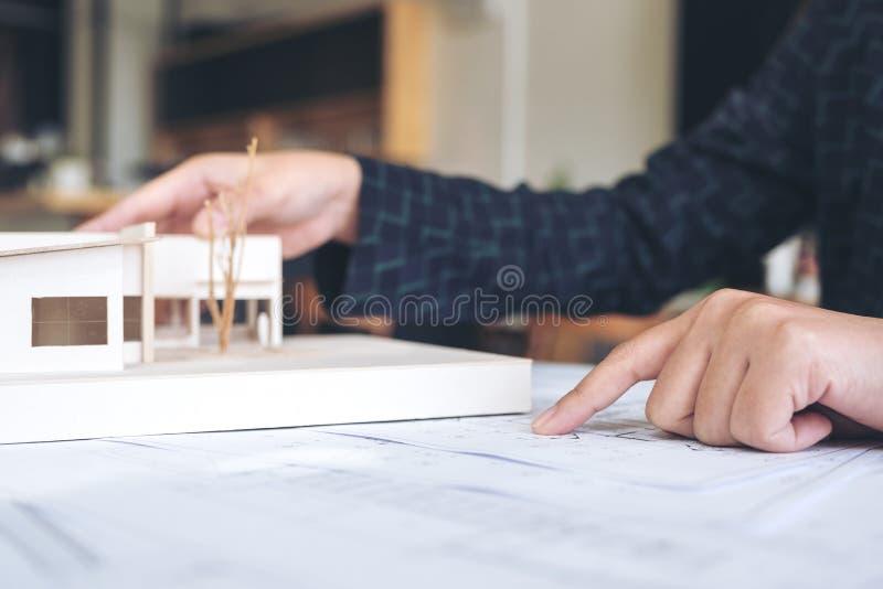 Um arquiteto que trabalha e que aponta no modelo da arquitetura com papel de desenho da loja fotografia de stock
