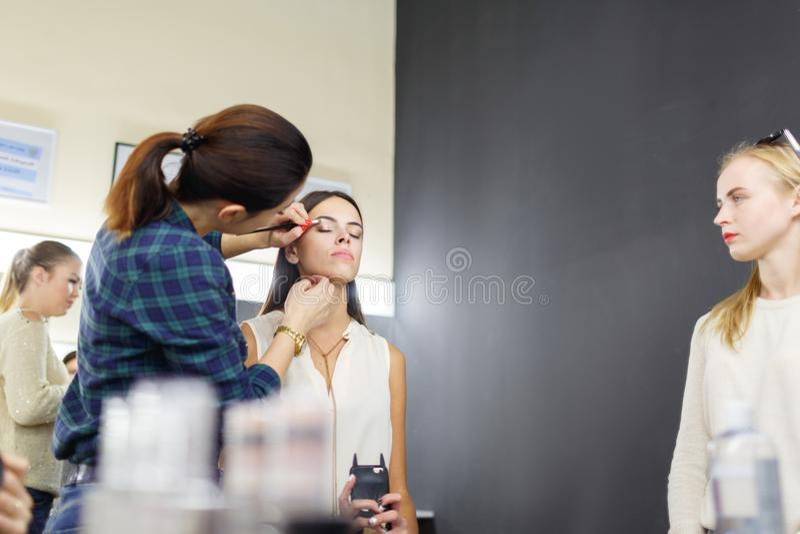 Um artista de composição está aplicando a composição a uma moça imagem de stock