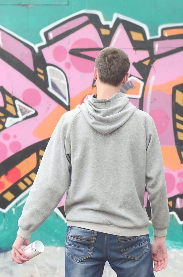 Um artista novo dos grafittis em um hoodie cinzento olha a parede com imagem de stock