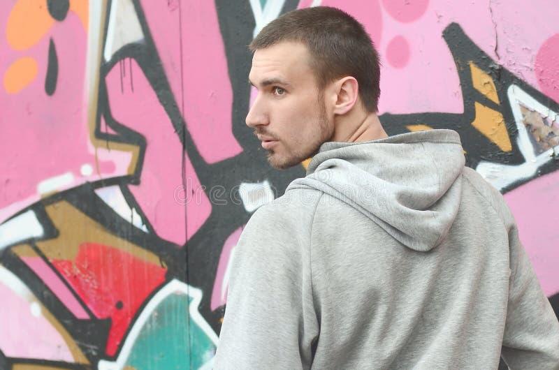 Um artista novo dos grafittis olha ao redor ao tirar Tentativas do v?ndalo fotografia de stock royalty free