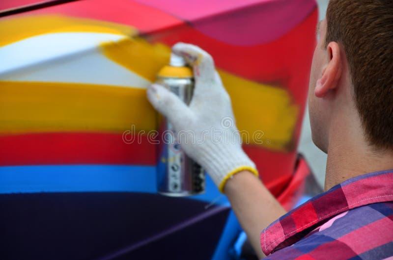 Um artista ruivo novo dos grafittis pinta um grafitti colorido novo no carro fotografia de stock royalty free
