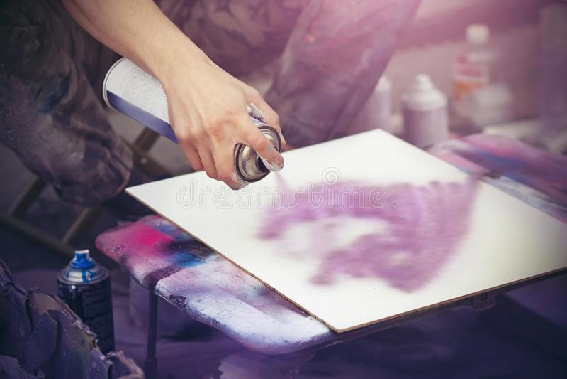 Um artista tira em uma lona branca com um grafitti cor-de-rosa da pintura à pistola foto de stock royalty free