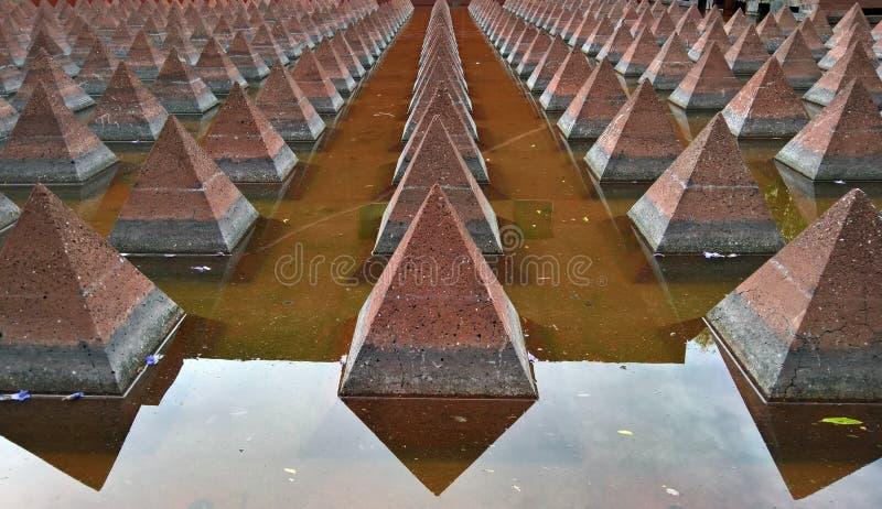 Um arty cem das pirâmides em uma lagoa de água imagens de stock