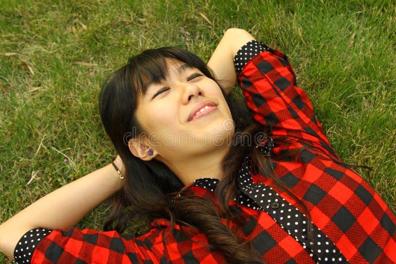 Um Asian que esteja dormindo na grama imagens de stock